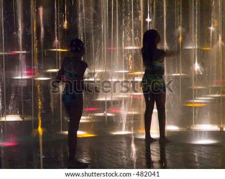 Two sisters in a fountain at night - stock photo