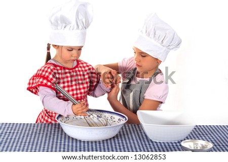 Two sisters in aprons and chef's hats making a cake
