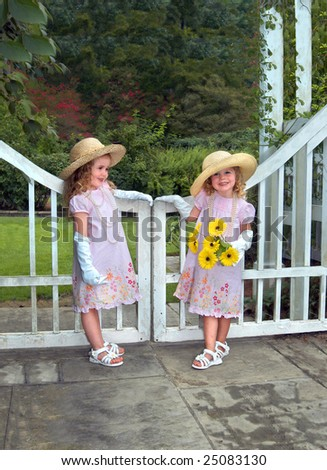 Two sisters in identical dressed and wearing straw hats and white gloves stand besides a white wooden gate in garden. - stock photo