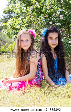Two sisters laughing and playing in the park, laying down. - stock photo