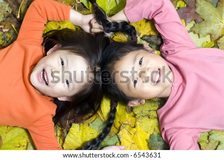Two sisters laying in a pile of autumn leaves - stock photo