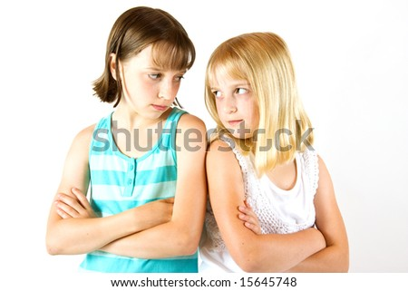 Two sisters looking at each other after a row, against white background