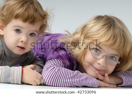 two sisters lying on the floor - stock photo