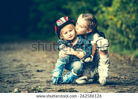 two sisters on roller skates in park - stock photo