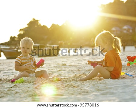 Two sisters play with sand. Koh Lipe island, Thailand