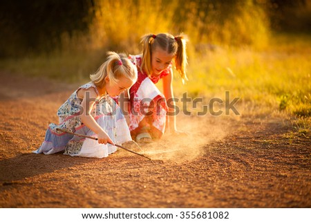 Two sisters playing in the dirt - stock photo