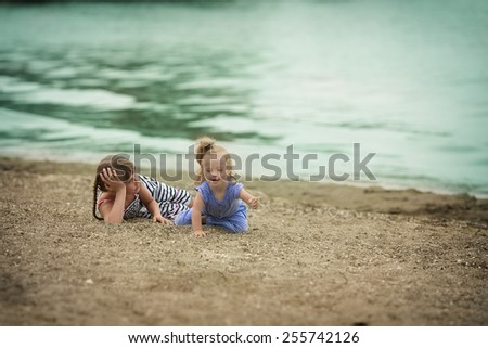 two sisters playing on the beach - stock photo