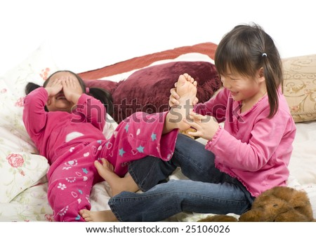 Two sisters playing on the bed, tickling feet.