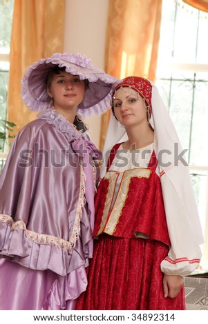 Two sisters poses in old russian dress indoor - stock photo