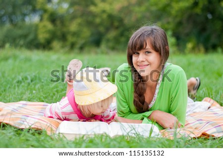 Two sisters reading a book outdoors - stock photo