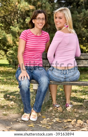 two sisters sitting on a bench - stock photo