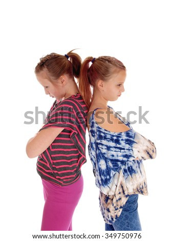 Two sisters standing back to back and are very mad to each others, isolated for white background. - stock photo