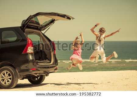 two sisters standing near a car on the beach - stock photo