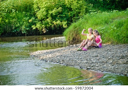 Two sisters throw stones into the river, have fun.