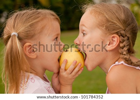 two sisters, together bite a pear - stock photo