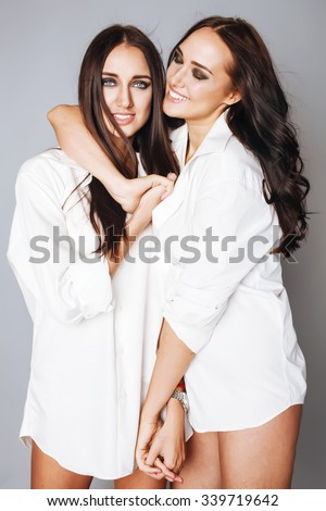 two sisters twins posing, making photo selfie, dressed same white shirt, diverse hairstyle friends smiling close up girlfriend sweety - stock photo