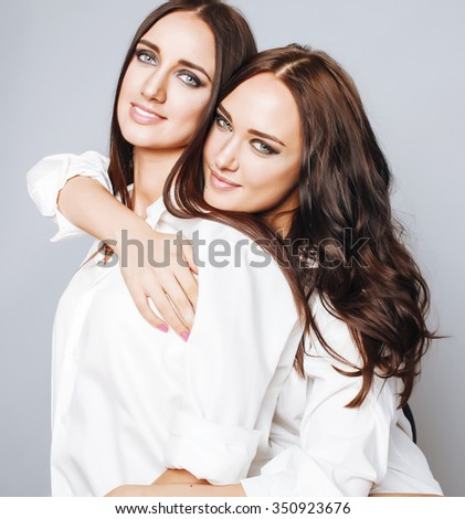 two sisters twins posing, making photo selfie, dressed same white shirt, diverse hairstyle friends smiling close up. sister friendship - stock photo
