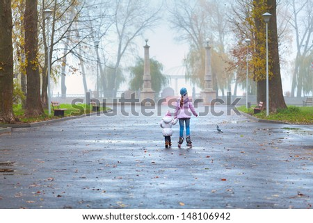 Two sisters walking in the autumn park - stock photo