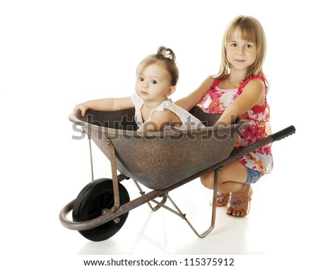 Two sisters with a wheelbarrow -- an adorable baby inside, her attractive elementary sister squatting behind it.  On a white background.