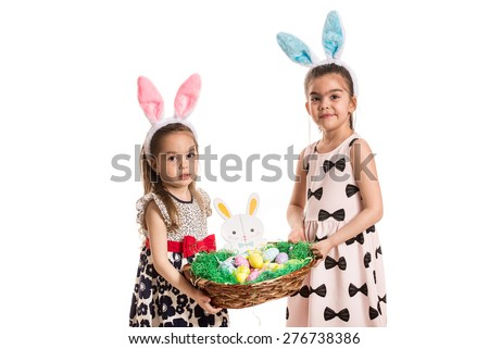 Two sisters with fluffy bunny ears holding basket with easter eggs isolated on white background - stock photo