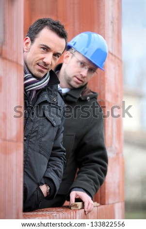 Two site workers hiding in unfinished house - stock photo
