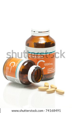 Two size of vitamin C bottle and pill with reflection - stock photo