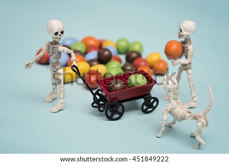 Two skeleton kids getting chocolate candy - stock photo