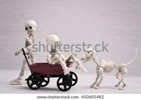 Two Skeleton playing red wagon and skeleton dog - stock photo