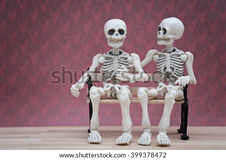 Two skeletons sitting on bench with red background