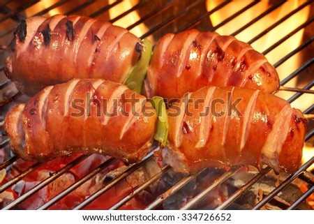 Two Skewers With Sausage On The Hot BBQ Charcoal Grill And Flames In The Background - stock photo
