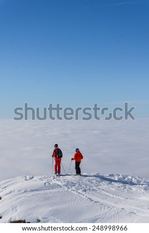 Two skiers standing on top of a mountain above the clouds