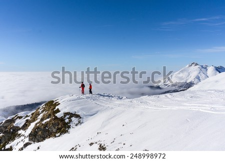 Two skiers standing on top of a mountain above the clouds - stock photo