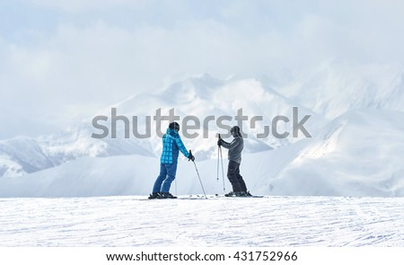 two skiers talking about something alone on a background of mountains. - stock photo