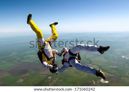 Two skydiver in freefall in the clouds. - stock photo
