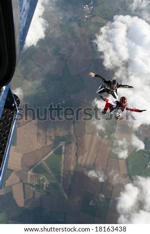 Two skydivers exit a plane in a sit position - stock photo