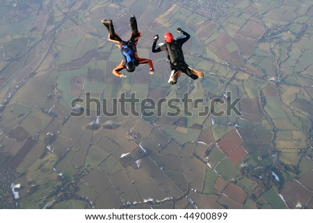 Two skydivers in free fall with snow in the background - stock photo