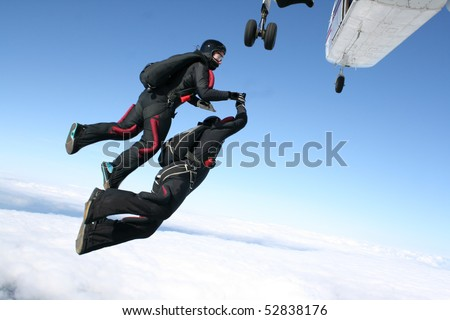 Two skydivers jump from a plane - stock photo
