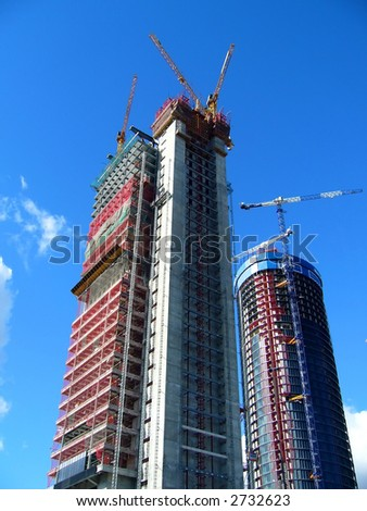two skyscrapers in construction over a shiny blue sky - stock photo