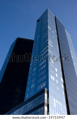 Two skyscrapers. One in sun light, one in shadow - stock photo