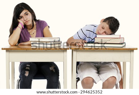 Two sleepy school kids at their school desk isolated on white.