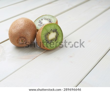 Two sliced kiwifruits or chinese gooseberry kiwi fruits composition over the white wooden boards surface - stock photo