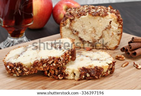 Two sliced of pecan and apple loaf cake in front of whole cake.  Apples and cider in the background. - stock photo
