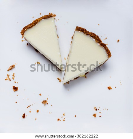 two slices of cheesecake on a white plate with crumbs - stock photo