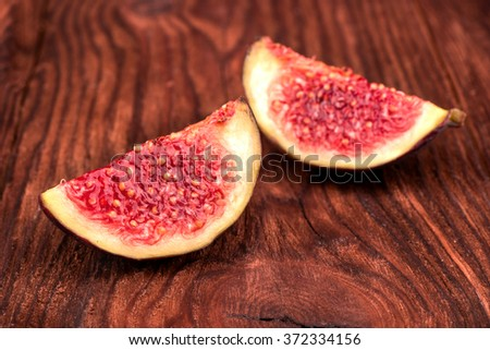 Two slices of fresh figs on a wooden background