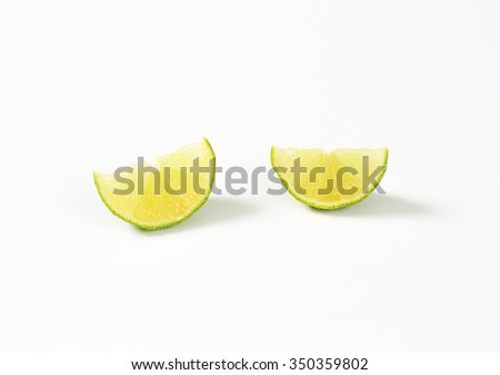 two slices of fresh lime on white background - stock photo