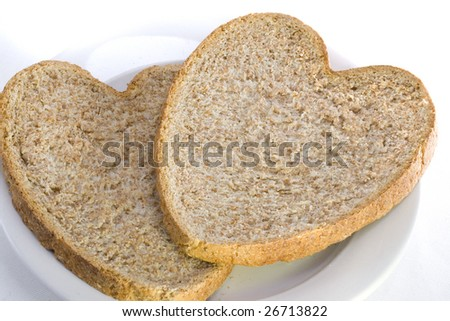 Two slices of healthy heart shaped wholemeal bread on a white plate. - stock photo