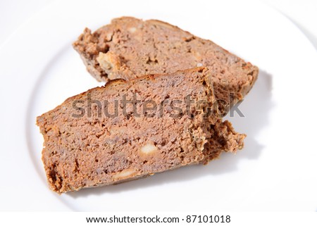 Two slices of homemade meatloaf on a white plate