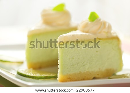 Two slices of silky key lime cheesecake presented with lime slices