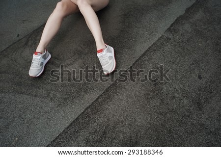 two slim legs in gray sneakers laying half-bent on roofing material or asphalt. - stock photo