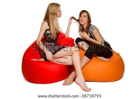 Two slim sexy girls sitting on bean-bags and talking, over white background
